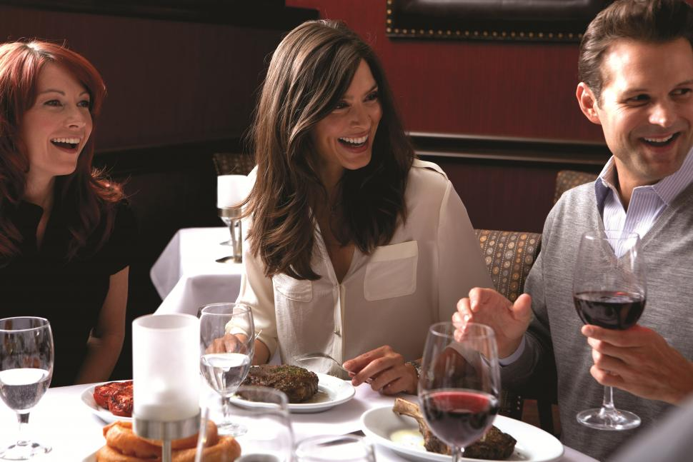 Group of people eating food and drinking wine at Ruth's Chris Steak House (photo: Ruth's Chris Steak House)