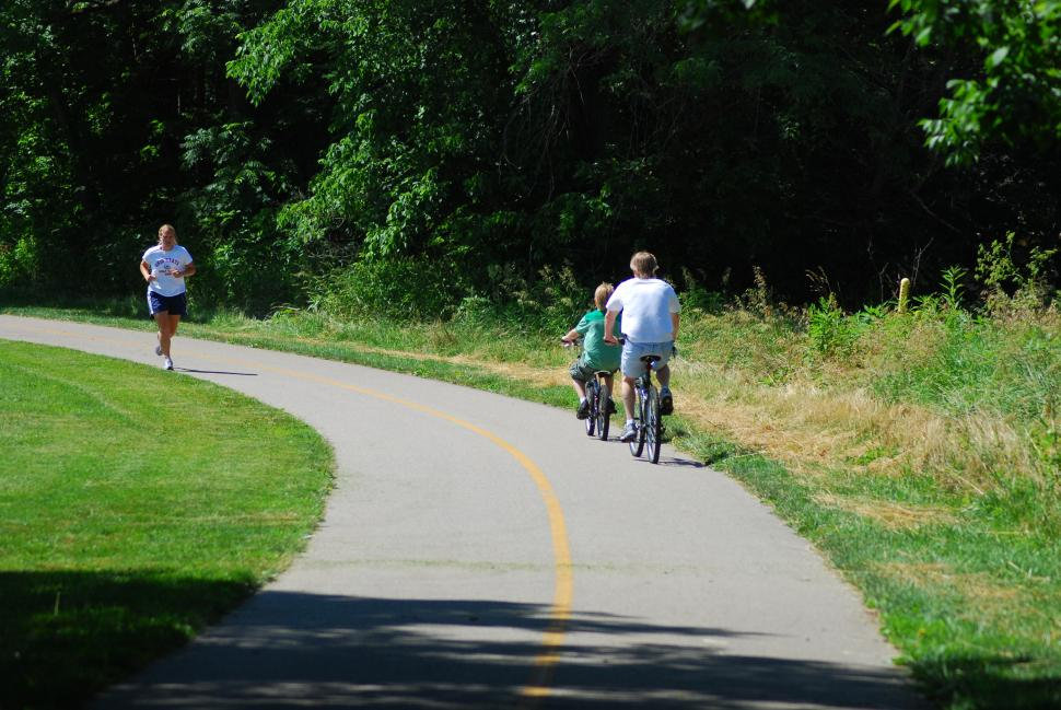 Two bikers and jogger enjoying the day in Miami Whitewater Forest